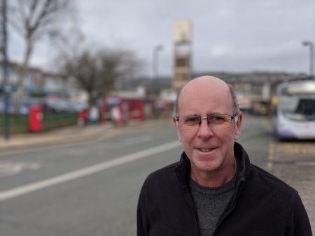 Councillor Martin Love stood in Shipley Market place with the clock tower in the bacground