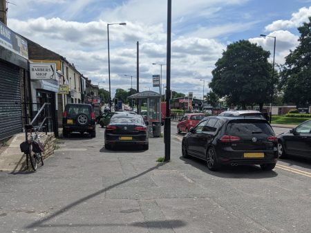 A number of cars parked dangerously on the pavement outside the shops on Tong Street