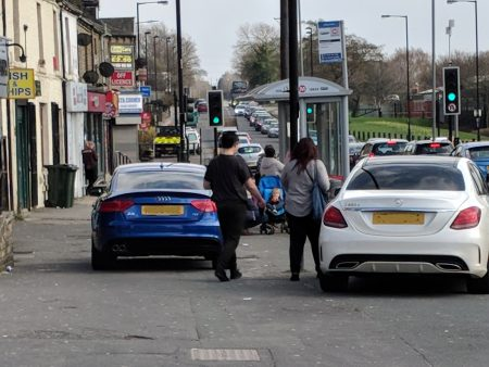Two premium cars blocking pavement on Tong Street whilst two pedestrians walk round