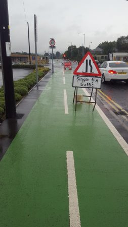 Road works sign placed in segregated cycle lane Stanley Road in Bradford BD2
