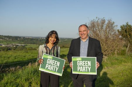 "Andrew Cooper and Hawarun Hussain holding ""Vote Green Party"" boards in a field over looking the Tong Valley"
