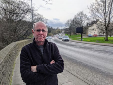 Councillor Martin Love stood next to Canal Road in Shipley with traffic in the background.