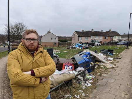 Matt Edwards standing next to a large amount of fly tipped rubbish outside houses on Melcombe Walk in Holmewood, Bradford.